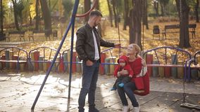 Young mom and dad with an infant playing on the playground. swings and carousels in the park for children stock video footage