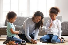 Young mom drawing together with small mixed race kids. Young mom with little mixed race kids sit on floor paint picture with colorful pencils, happy mother spend royalty free stock images