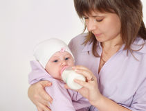 Young mom feeding baby Royalty Free Stock Image