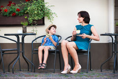 Young mom having coffee with her son. In street cafe Stock Photos