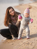 Young mom helping small daughter to walk on beach Stock Photo