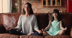 Young mom her daughter do meditation practice at home