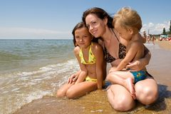 Young mom and her kids at the beach. Mom and her children enjoying their vacation at the seaside Royalty Free Stock Photos