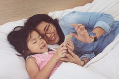 Young mom and her little daughter are using a smartphone. On bed at home stock photos