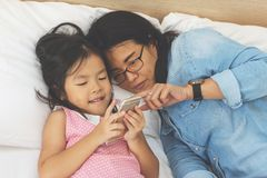 Young mom and her little daughter are using a smartphone on bed. At home royalty free stock images