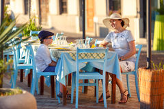 Young mom and her son in street cafe. Young mom and her cute little son in street cafe Royalty Free Stock Photos