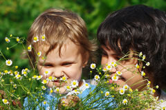 Young mom with her son among the summer daisies Stock Images