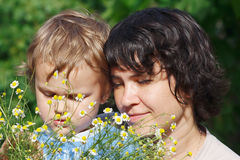 Young mom with her son among the summer daisies Stock Photo