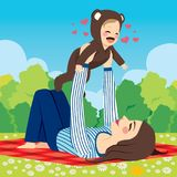 Mom Baby Park. Young mom holding up cute baby wearing bear outfit at park lying on blanket Royalty Free Stock Photography