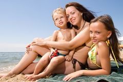 Young mom with kids at the beach resort. Mom and her children enjoying their vacation at the beach Stock Photography