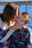 Young mom kissing her adorable son's cheek Royalty Free Stock Photos