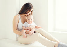 Young mom kissing her baby at home in light room Stock Photography