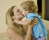 Young mom kissing her son. Young beautiful mother holding her son and kissing him in the mouth Royalty Free Stock Photography
