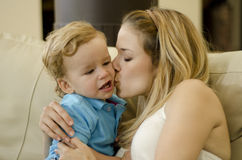 Young mom kissing her son. Cute young mother kissing her son on his cheek Stock Image