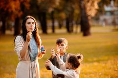 Young mom and little children playing with soap bubbles. In a park Stock Image