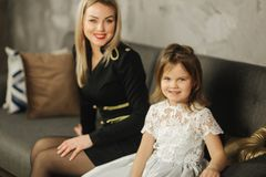 Young mom and little daughter at home sitting on sofa. Attractive mother in black dress. Happy family royalty free stock images
