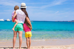 Young mom and little girls at white beach on sunny Stock Photos