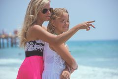 Young mom is making pointing gesture showing something her daughter on the sea. Young mom is making pointing gesture showing something her daughter on the sea stock photography