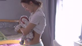Young mom with newborn baby in her arms stock video footage