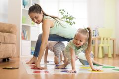 Mother playing twister with her children daughters. Happy family have a fun time in holiday Royalty Free Stock Photos