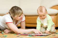 Young mom reading her little son book on a floor Royalty Free Stock Photo
