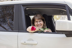 Young mom sitting in her car holding a red rose. Stock Image
