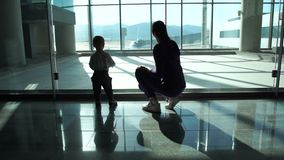 Mom and small son look at the planes through the large windows at the airport. Young mom and small son look at the planes through the large windows at the stock video