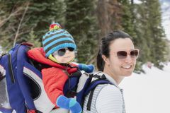 Young Mom Snowshoeing with her Baby in a Backpack. In a Beautiful Mountain Setting stock photography