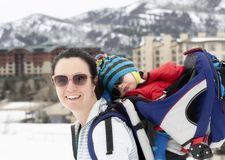 Young Mom Snowshoeing with her Baby in a Backpack. In a Beautiful Mountain Setting stock photos