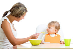 Young mom spoon feeding her cute baby girl Royalty Free Stock Photos