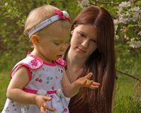 Young Mom and Toddler Looking at Flower. This young mom is watching her toddler girl hold and look at a buttercup flower outside Stock Photo