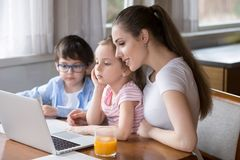 Young mom watch cartoons on laptop with daughter and son stock images