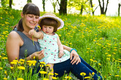 Young mommy and her baby laying on the grass and hugging Stock Image