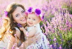 Mom and her daughter in a lavender field. Young mommy and her little daughter in a beautiful wreath are walking in a lavender field. Life in Provence. Brunette Royalty Free Stock Photos
