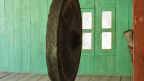 Young monk beats in big gong in nepalese village Lho, Nepal. Young monk beats in big gong in nepalese village Lho, Nepal stock footage