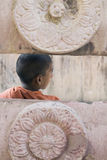 Bodhgaya, India, Young Monk at Mahabodhi temple. Young Buddhist Monk through the Ancient Stone Fence at the Mahabodhi Temple, Bodhgaya, India Royalty Free Stock Photo