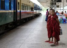 Young Monk Boys Myanmar. Yangon, Myanmar - July 28: Two unidentified young novice monks waiting on the train at the Central Railway Station in Yangon, Myanmar on Stock Images