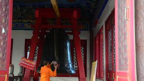 Young monk hitting the largest Bell for pray. In the evening in Chinese temple at Nonthaburi Thailand stock footage