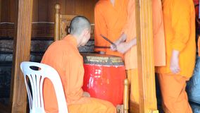 Young monk hitting the largest drum for pray in the evening stock video footage