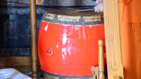 Young monk hitting the largest drum for pray in the evening. In Chinese temple at Nonthaburi Thailand stock footage