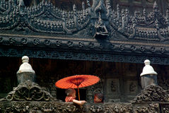 Young monk holding umbrella at Shwenandaw Monastery in Mandalay. Stock Photos
