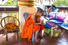 Young monk listen to music inside the Wat Suan Dok Temple, Chiang Mai, Thailand. royalty free stock images