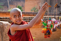 A young monk playing with puppets in Bagan, Myanmar Stock Photos