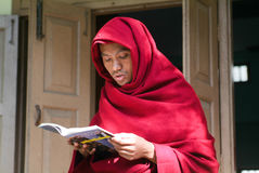 Young monk reading a book at Mahagandayon Monastery on Mandalay, Royalty Free Stock Photo