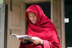 Young monk reading a book at Mahagandayon Monastery on Mandalay, Royalty Free Stock Photo