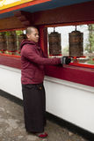 An young monk. An young student monk is moving prayer wheel at Enchey Monatery, Sikkim, India Royalty Free Stock Photography