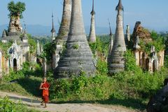Young monk between stupas. Young monk walkng between stupas Royalty Free Stock Photography