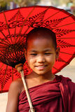 A young monk with the umbrella in Mandalay, Myanmar Stock Photo
