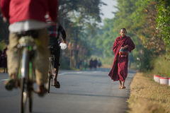 Young monk walks along road to collect alms. Stock Image