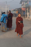 Young monks get food offerings in early morning Royalty Free Stock Image
